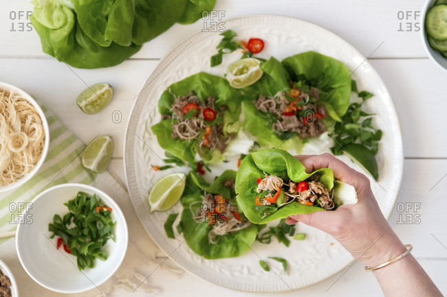 A person picks up a Asian beef and noodle lettuce wrap