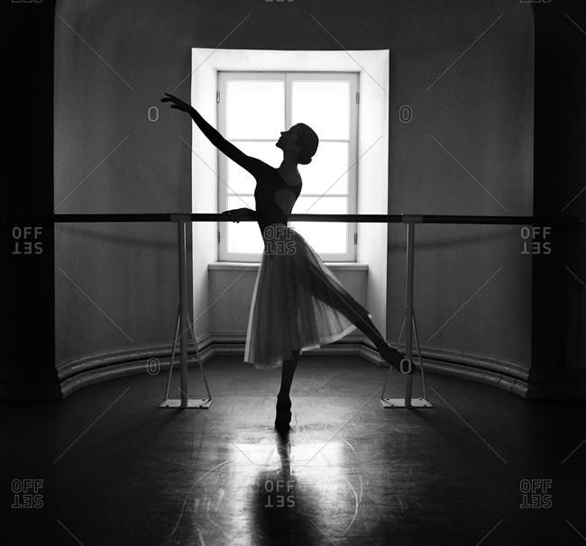 Female ballet dancer at barre in front of window