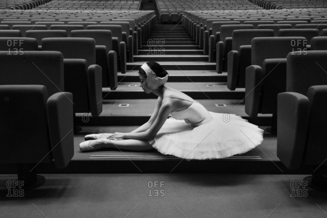 Dancer in Swan Lake costume stretching in aisle of theater