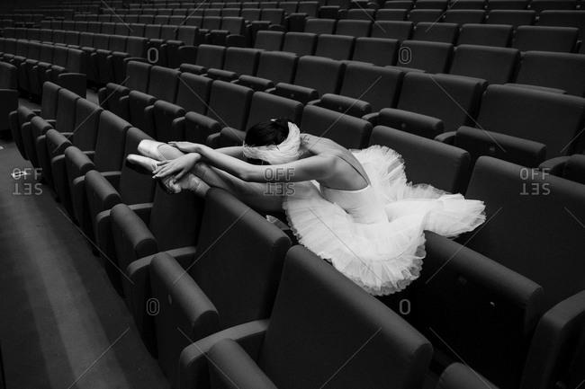Costumed ballet dancer resting in theater seats