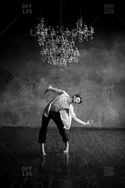 Male ballet dance dances below chandelier