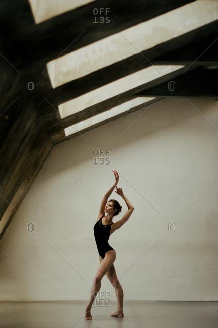 Dancer beneath skylights in modern building