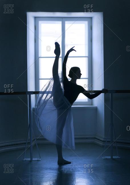 Ballet dancer on one leg at barre