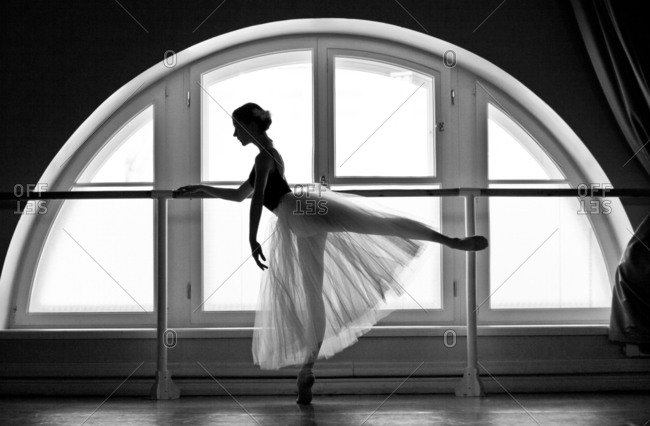 Ballet dancer with leg out behind her at barre