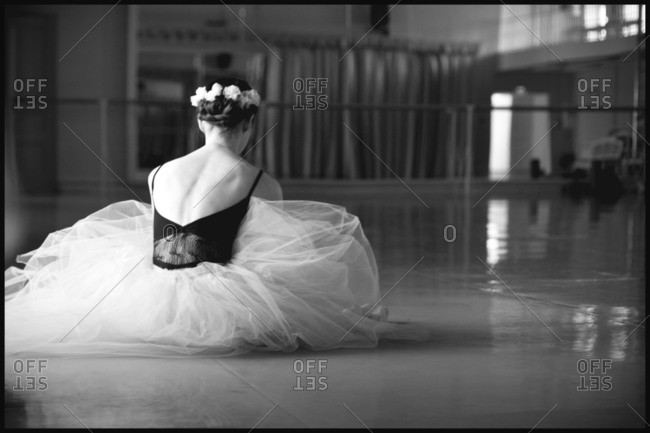 Back of a costumed ballerina seated on the floor of dance studio