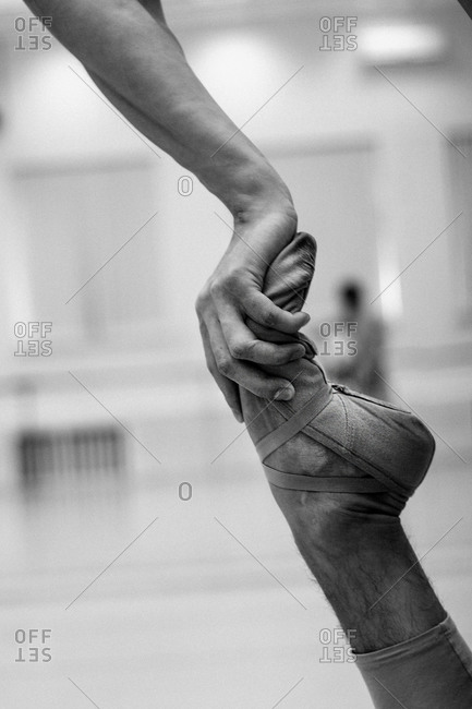 Hand pressing on a male dancer's foot