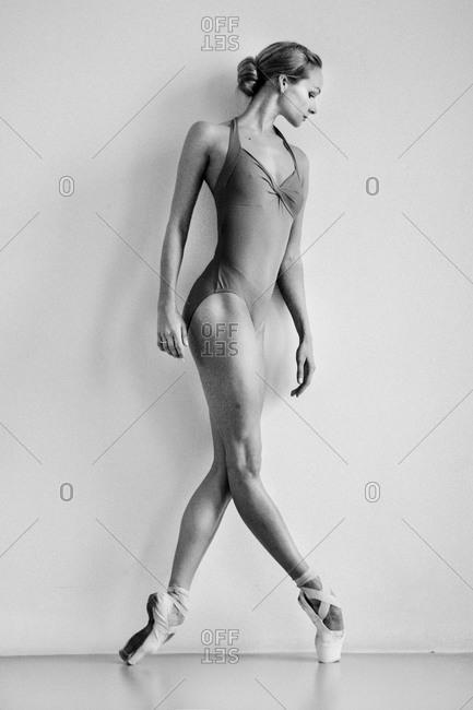 Ballet dancer en pointe against a white wall