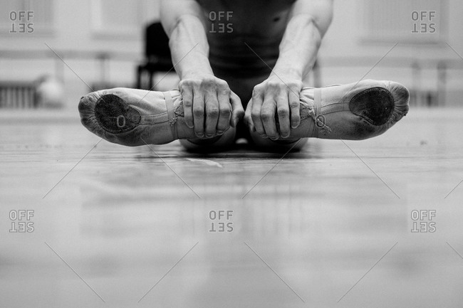 Male dancer holding onto his heels while stretching his feet out to the side
