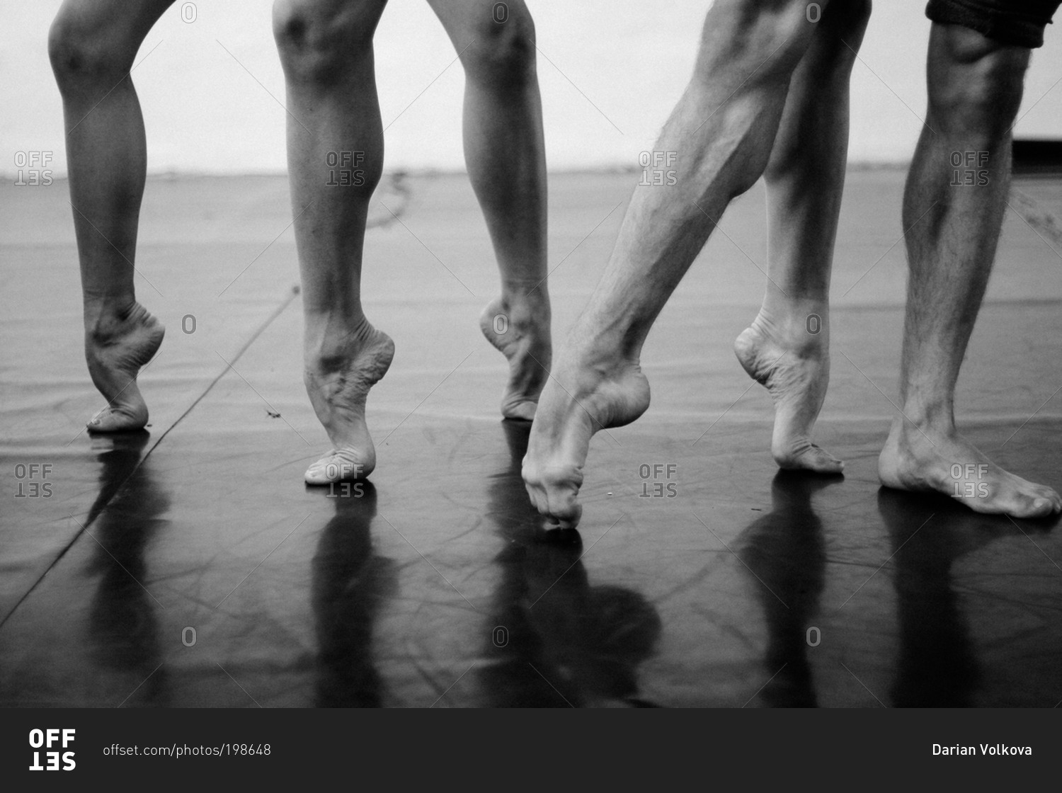 Muscular Legs Of Three Male Dancers Stretching Their Feet Stock