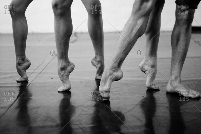 Muscular legs of three male dancers stretching their feet