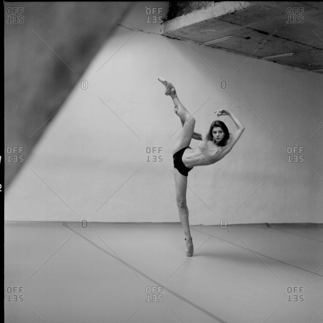 Dancer balancing on one leg, while holding the calf of the extended leg