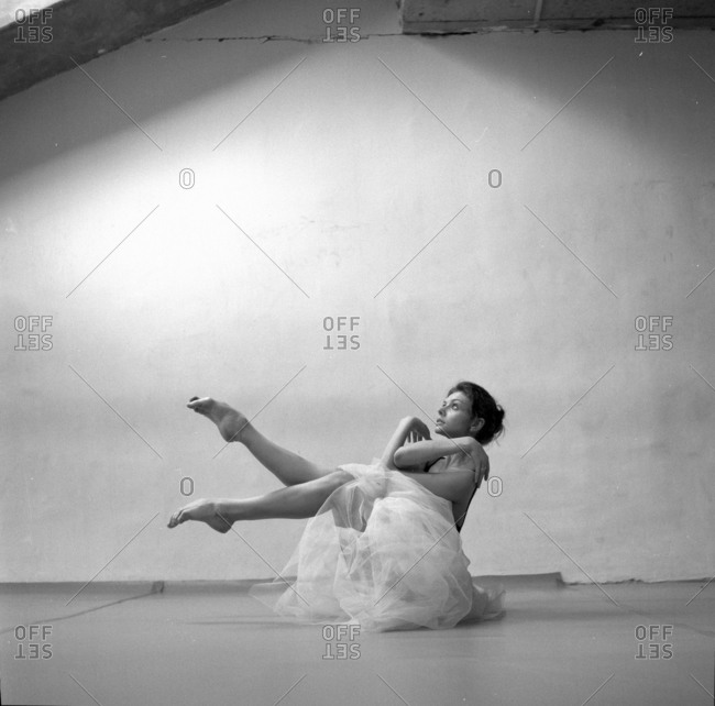 Female ballet dancer seated on floor with legs up