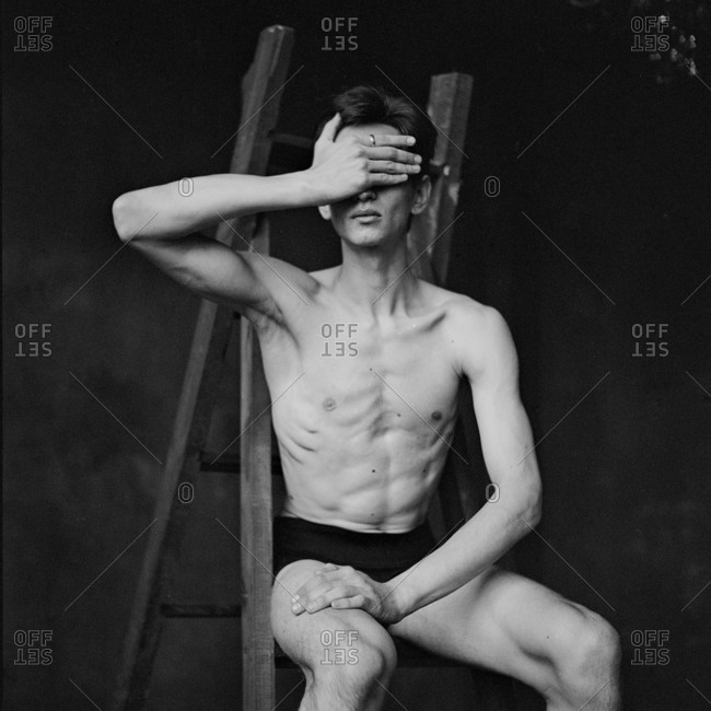 Male dancer seated on a ladder covering his eyes