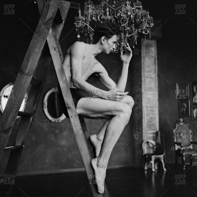 Male dancer seated on a ladder in a formal room