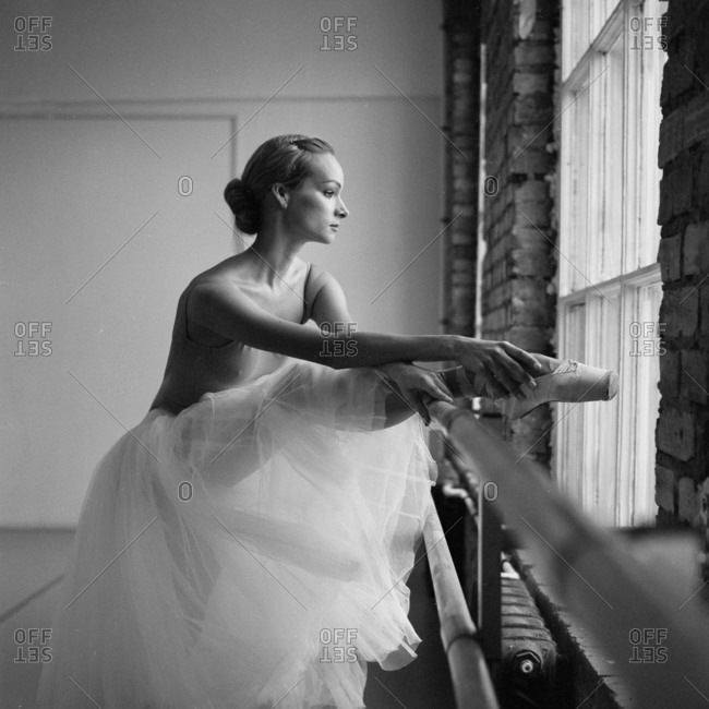 Ballet dancer stretching her leg on a barre