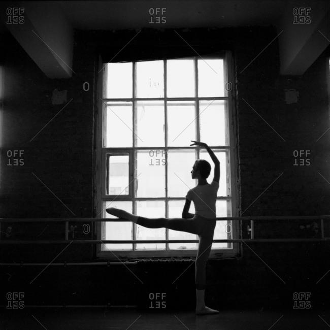 Male dancer stretching leg on a barre