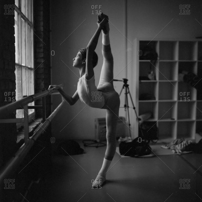 Ballet dancer at barre holding foot above head