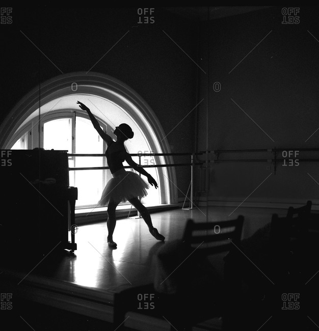 Silhouetted dancer practicing in studio