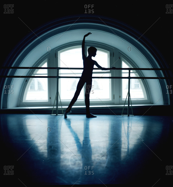 Male dancer silhouetted at barre in front of arched window