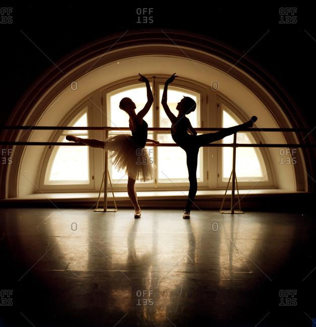 Pair of dancers in arabesque in front of window