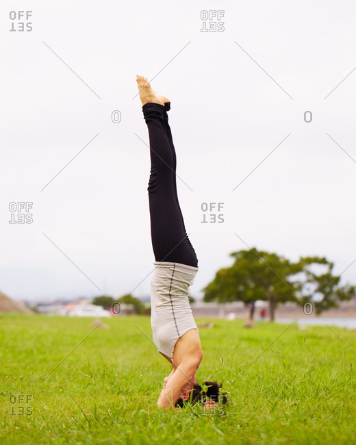 Young woman doing headstand in a park