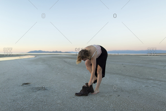 A young woman moves around the barren desert landscape of the Great Salt Lake, Utah