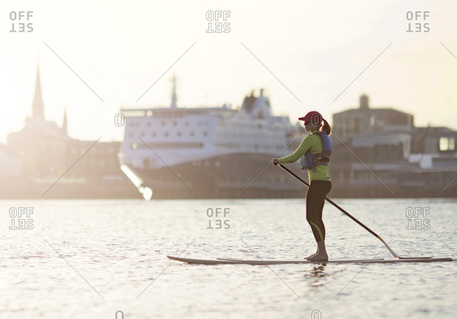 A young woman paddleboards across the harbor in Portland, Maine