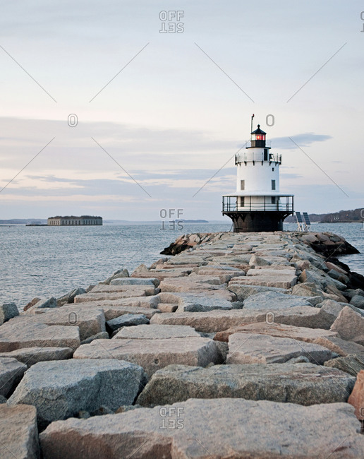 A lighthouse stands guard over the entrance to a harbor, Maine