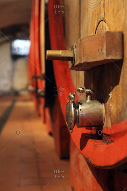 Siena, Italy - September 12, 2013: Wooden wine barrels sit in the wine cellar at Barone Ricasoli winery, the oldest winery in Italy