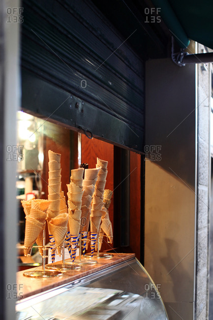 Ice cream cones of all shapes and sizes sit in a window of a gelateria