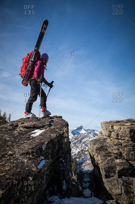 A woman backcountry skier hikes a snow free ridge to access high elevation skiing in the Bitterroot Mountains near Hamilton, Montana