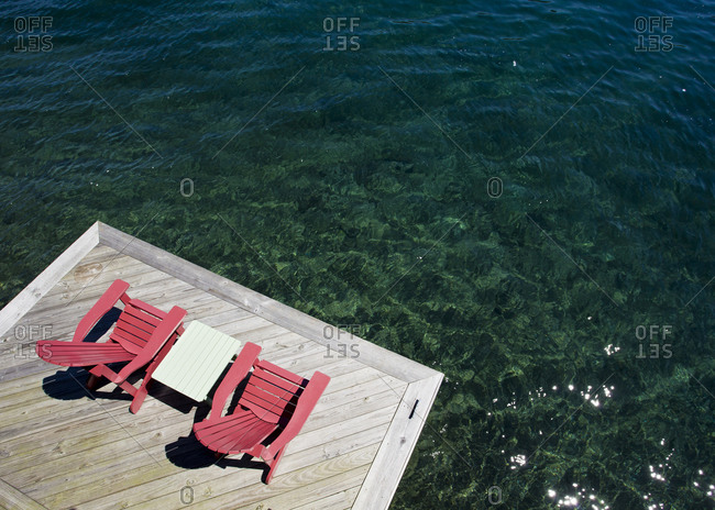 Two red chairs sit on a dock by Skaneateles lake