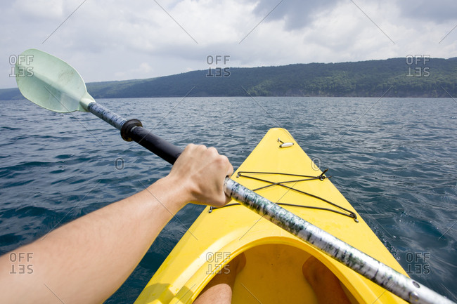 A man paddles a kayak into the middle of Skaneateles Lake, NY