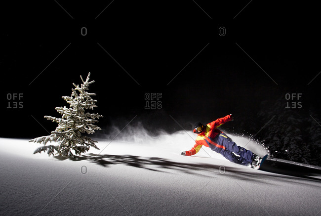 Snowboarder rides powder at night