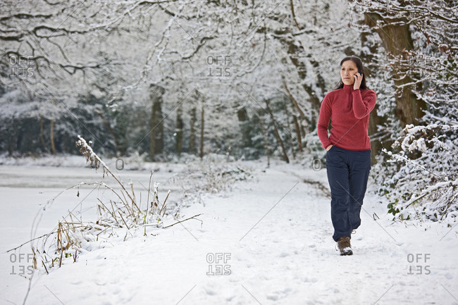 Woman talking on her mobile phone whilst walking through a wintery landscape next to the Basingstoke canal in Surrey, England