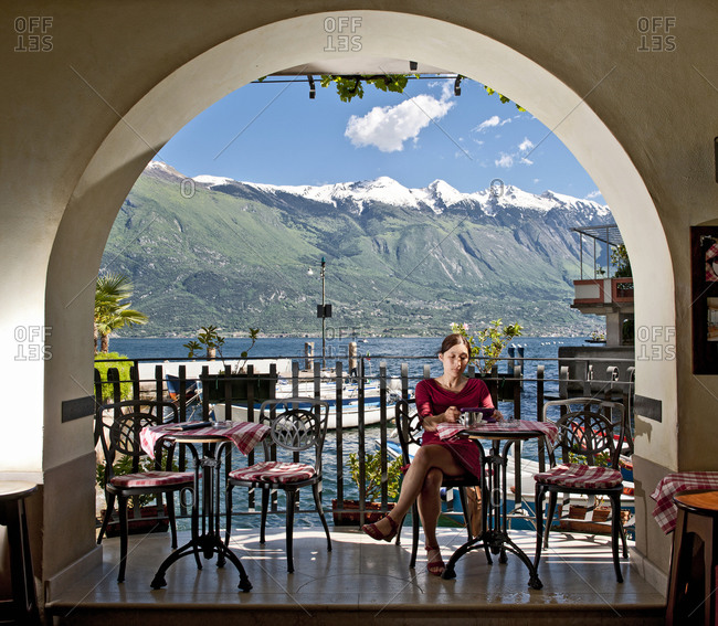 Woman sitting in street cafe in Limone at the Garda Lake in north Italy