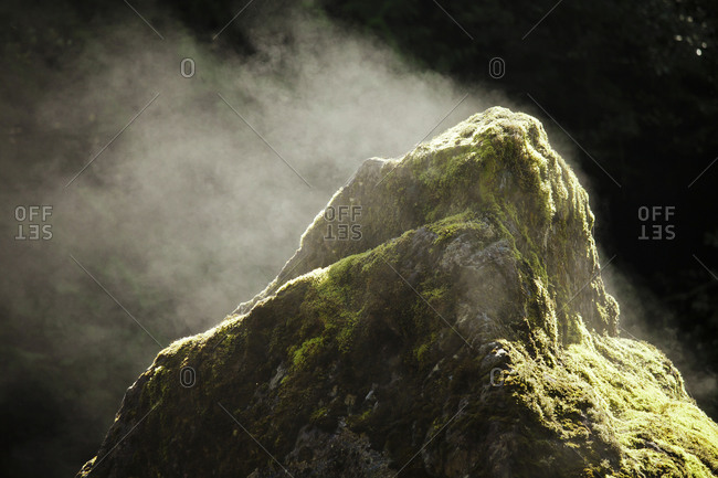 Sun causes evaporation and steam to come off a large boulder