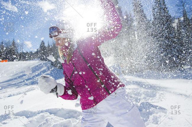 A woman having a snowball fight with friends