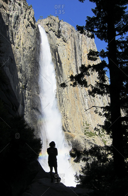 A woman looks out on the rushing waters of Yosemite Falls, Yosemite Valley, California