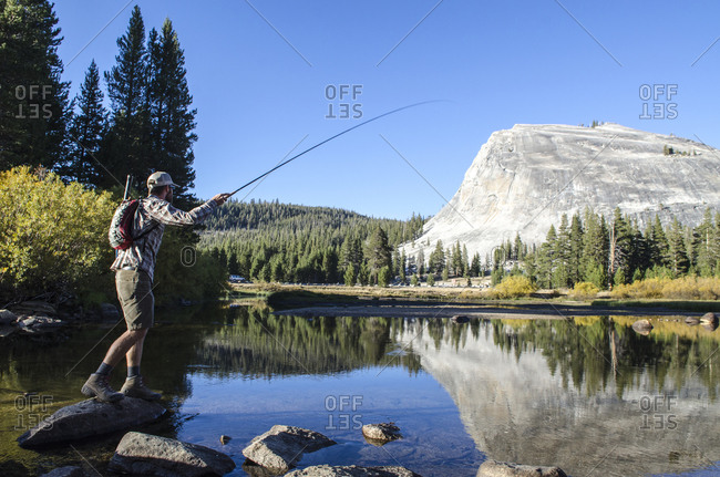 A young man fly-fishes in Tuolumne Meadows, California