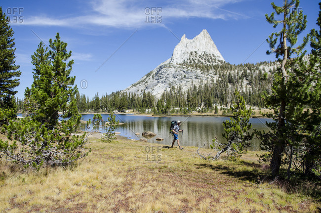 A young man walks past Cathedral Lake during a 273 mile backpacking trip from Tuolumne Meadows to Yosemite Valley, California