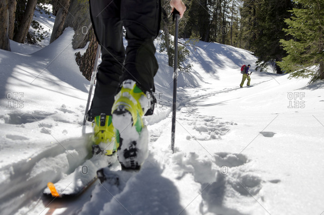 Two young men ski up a hill in the Lake Tahoe backcountry, Nevada