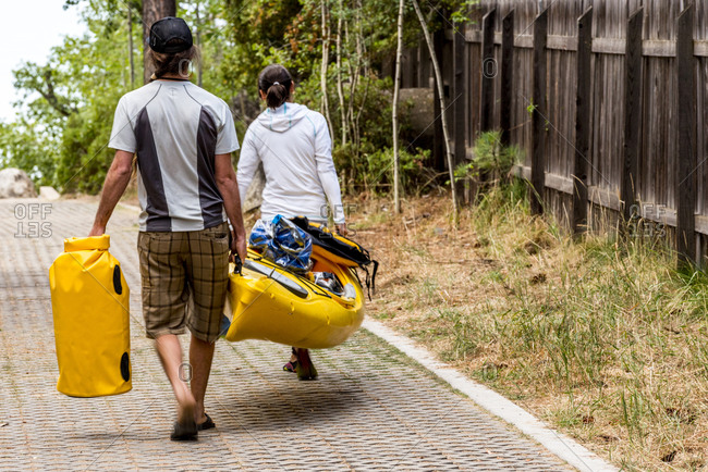 Two people carrying kayak and gear