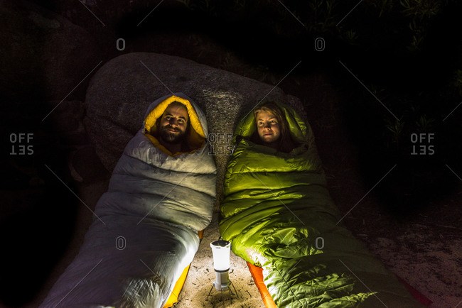 Man and a woman in sleeping bags by a lantern at night