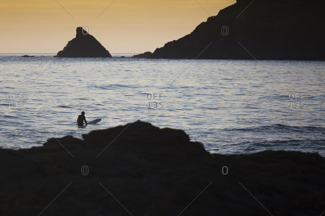 Lone Surfer waiting for waves at dusk, Summer, Cornwall, UK