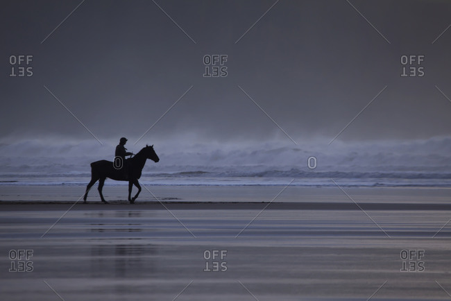 Silhouette of lone lady riding her horse along the beach, Woolacomb, North Devon, Uk