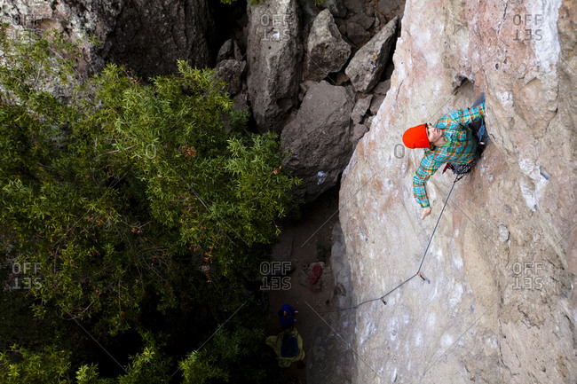 A male climber in an orange beanie and multicolored shirt climbs Family Jewel (510d) on Mount Gorgeous in Malibu Canyon State Park in Malibu, California