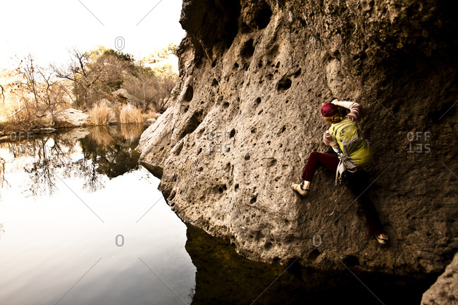 A male climber works his way across the Rock Pool traverse at Malibu Canyon State Park in Malibu, California