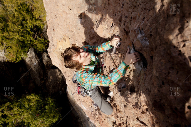 A male climber climbs Family Jewel (510d) on Mount Gorgeous in Malibu Canyon State Park in Malibu, California