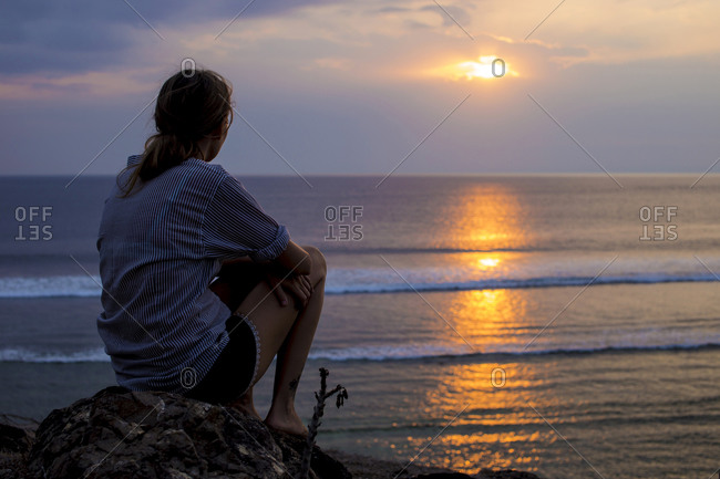 Woman looks at sunset in the ocean